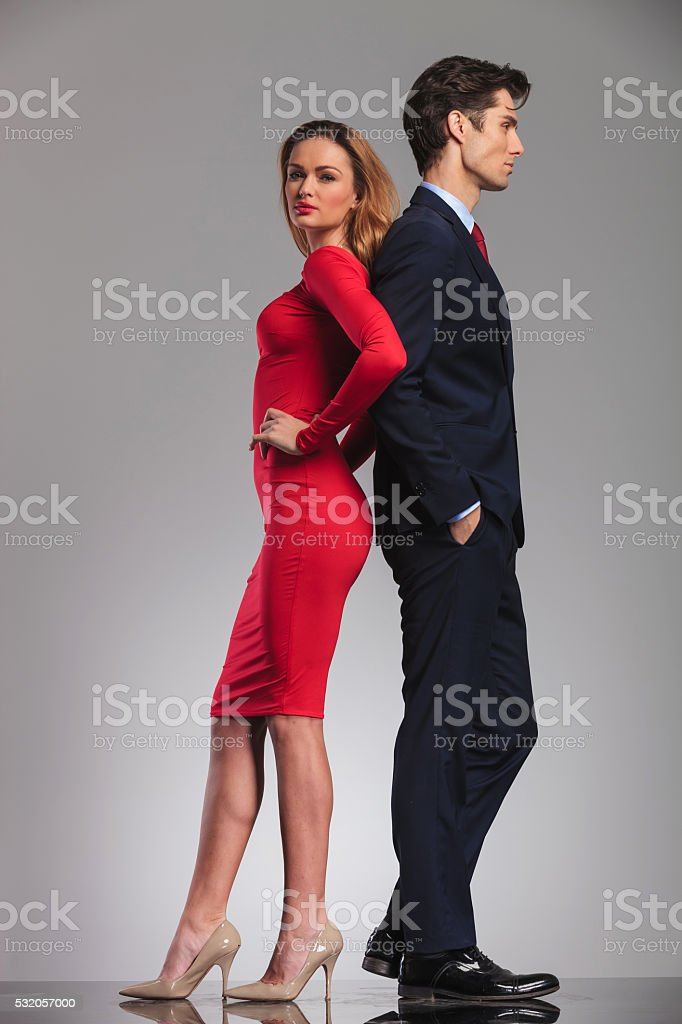 young elegant couple standing back to back in studio stock photo