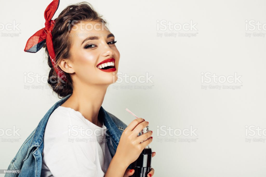 Young elegant female drinking cola stock photo