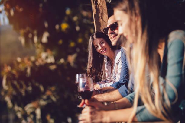 elegante junge freunde weinprobe im rustikalen ferienhaus patio - genießen französisch stock-fotos und bilder