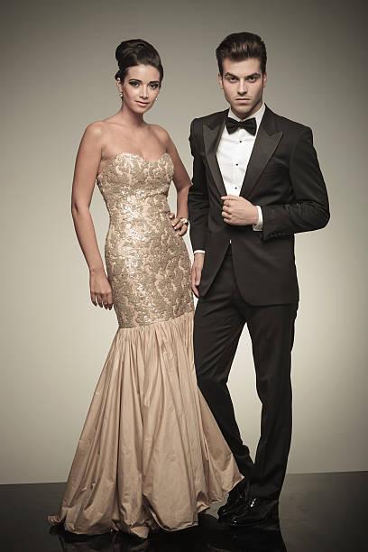 young elegant man and woman posing - knotenkleid stock-fotos und bilder