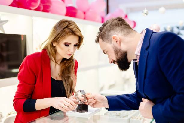 Young elegant man buying wrist watch in jewelry store Young elegant man buying wrist watch in jewelry store. Customer service in jewelry store jeweller stock pictures, royalty-free photos & images