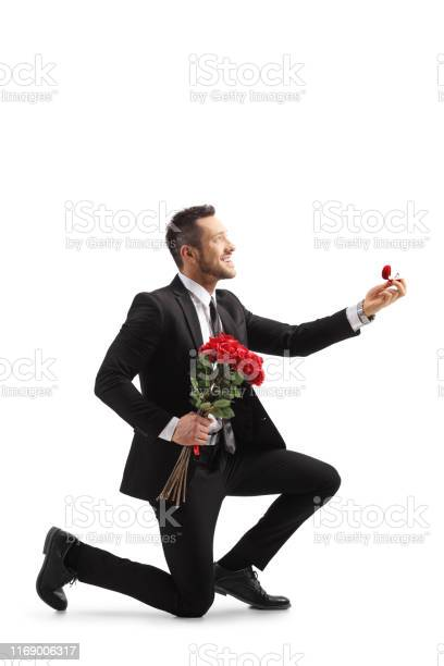 Young elegant man in a suit kneeling and holding roses and an ring picture id1169006317?b=1&k=6&m=1169006317&s=612x612&h=eedb0vkplevd9g4sxtwshhbzo 5zs5ct5gpz3trpxaa=