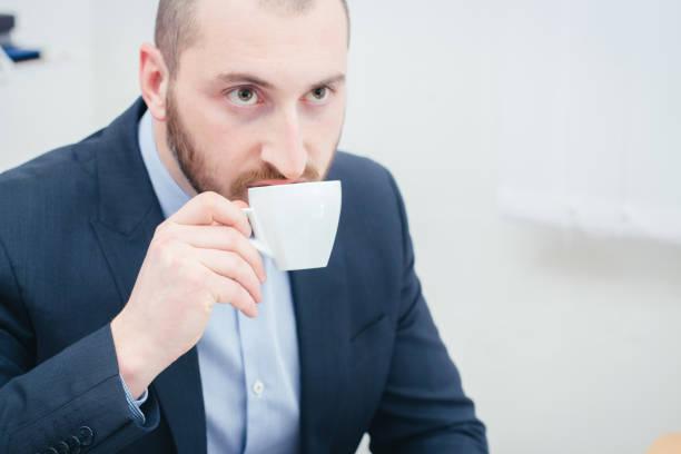 우아한 젊은이 사무실에 앉아서 커피를 마시는 휴식 시간에 한 벌에서. - 커피 마실 것 뉴스 사진 이미지