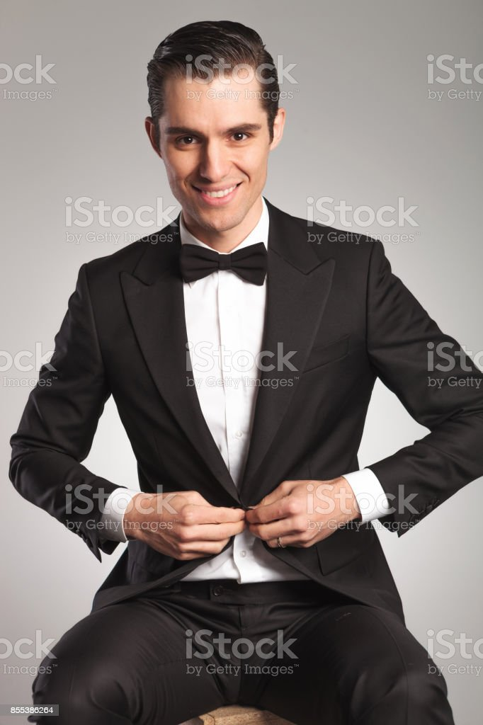 a93d2c5f3a74 young elegant man unbuttoning his tuxedo while sitting royalty-free stock  photo