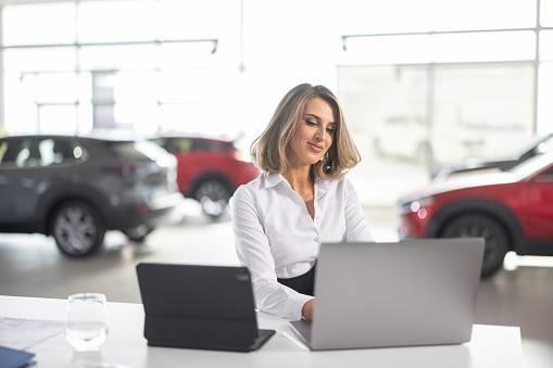 Young well dressed sales woman sitting at desk in car dealership saloon and using laptop