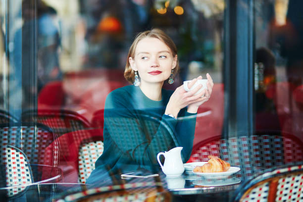 Young elegant woman drinking coffee in cafe in Paris, France Young elegant woman drinking coffee in traditional cafe in Paris, France french culture stock pictures, royalty-free photos & images