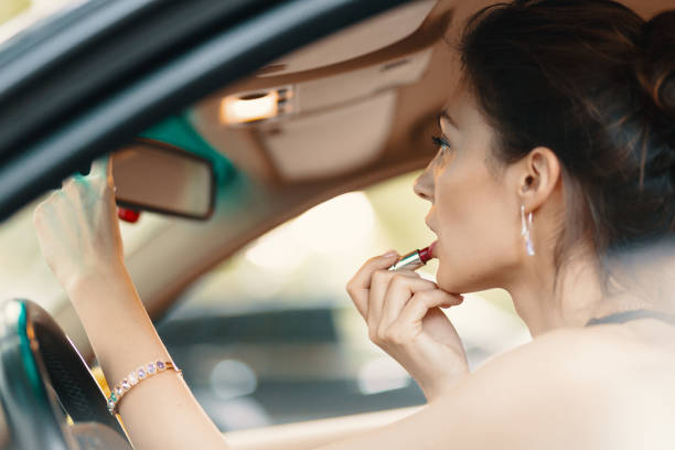 Young elegant woman looking in the car view mirror while applying makeup, lipstick on the lips Young elegant woman looking in rear view mirror painting her lips doing applying make up while driving the car. diva human role stock pictures, royalty-free photos & images