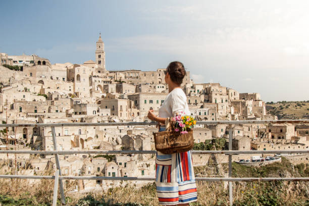 Young elegant woman tourist in historical Matera town in Italy walking looking at city landscape from railing Young elegant woman tourist in historical Matera town in Italy walking looking at city landscape from railing matera italy stock pictures, royalty-free photos & images