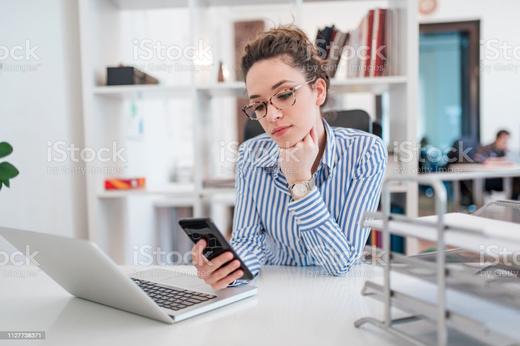 Young elegant woman using smart phone while sitting in front of laptop at bright office space. Modern business woman with glasses wearing blouse with stripes sitting at the work desk using mobile phone. - Royalty-free Adult Stock Photo