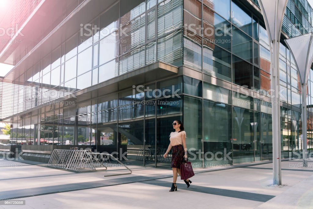 Young elegant woman walking in front of office building royalty-free stock photo