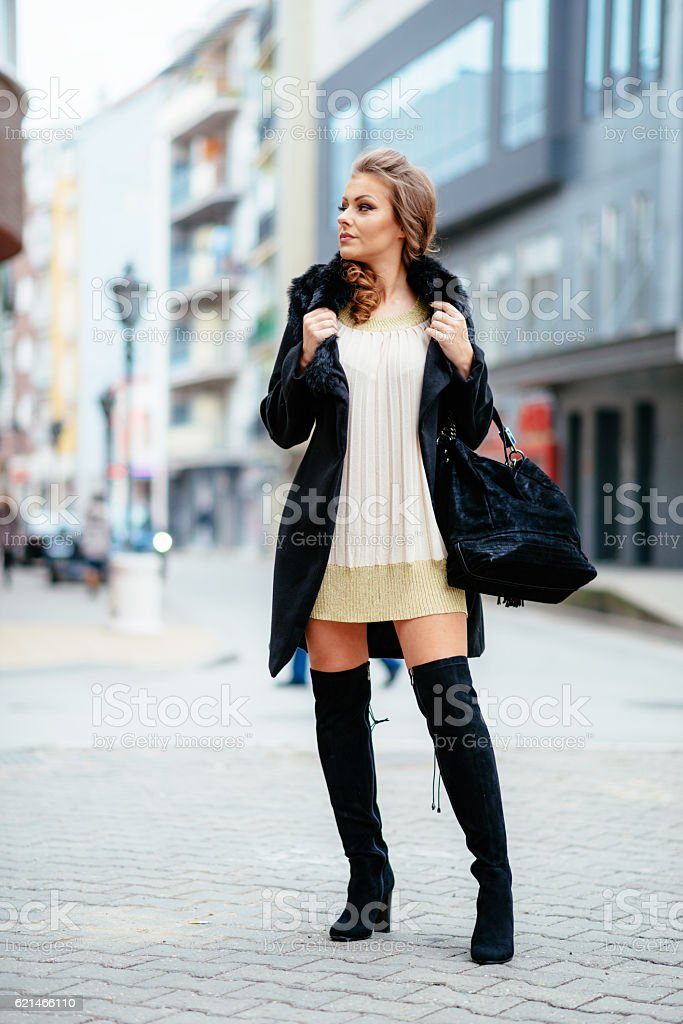 Young elegant woman wearing dress and black coat stock photo