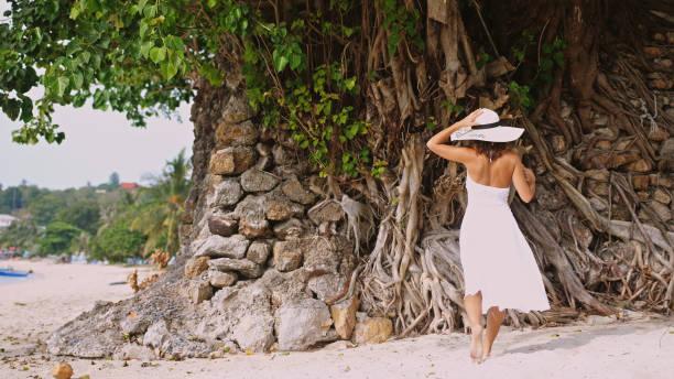 elegante mädchen mit langen haaren in weißen drees und hut am tropischen strand zu fuß - drees und sommer stock-fotos und bilder