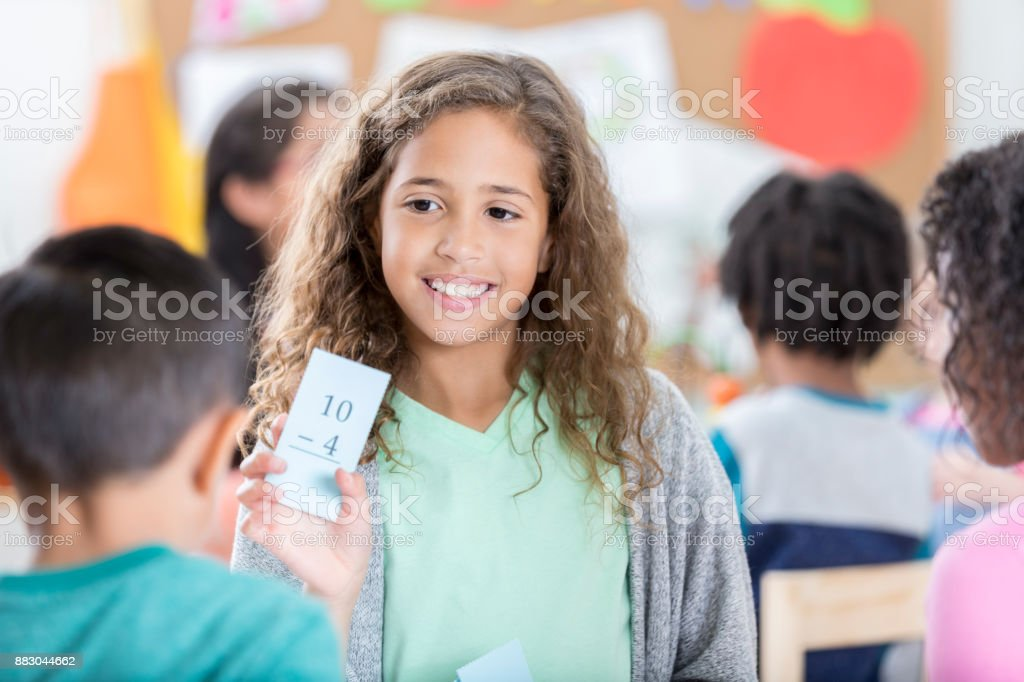 Young elementary age girl quizzes friend with math flash card stock photo