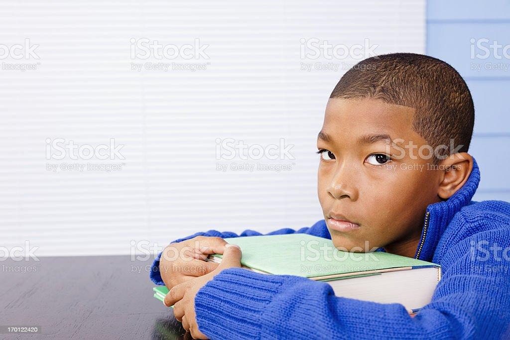 Young elementary aged boy procrastinating homework or depressed stock photo