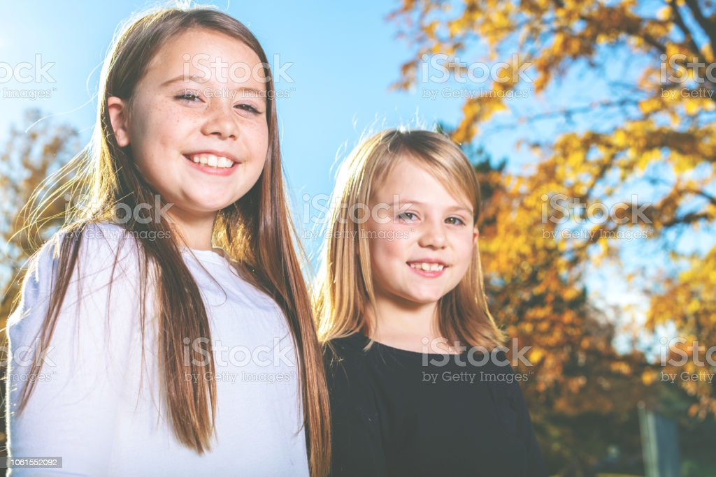 Young Elementary Aged Girls Outdoors in Autumn Happy Sisters in Western Colorado Park Area stock photo