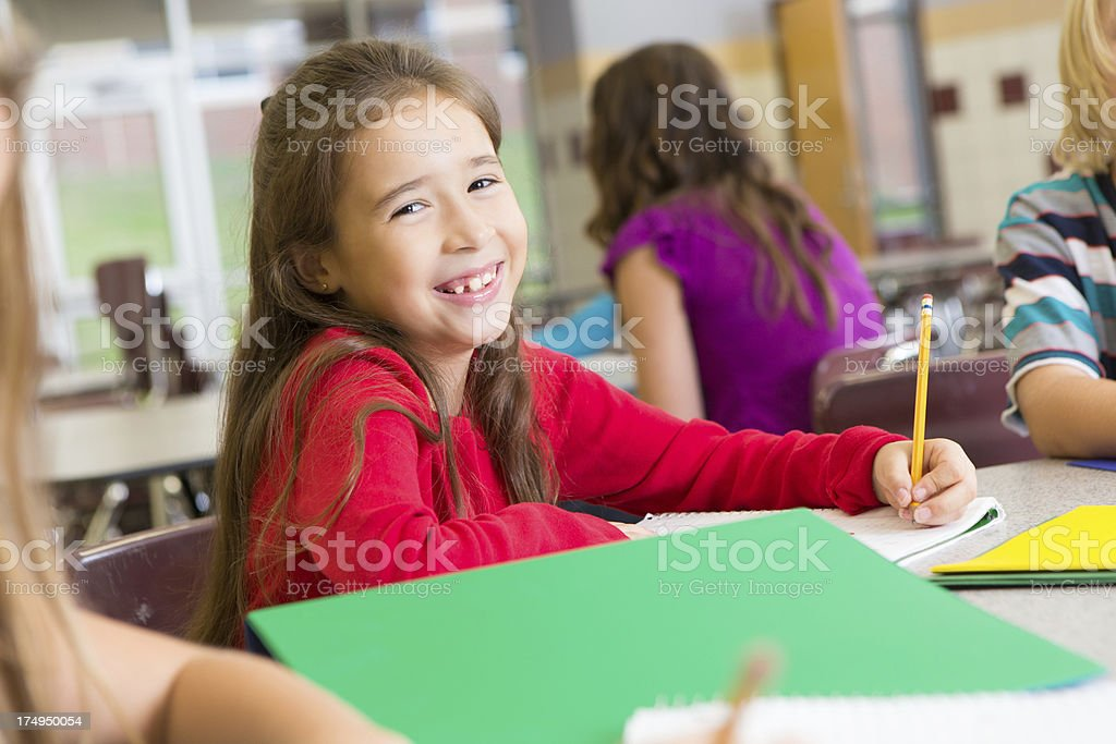 Young elementary student smiling while doing classwork at school royalty-free stock photo