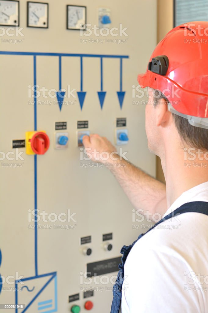 Young Eletrician Touching a Switch on the Panel stock photo