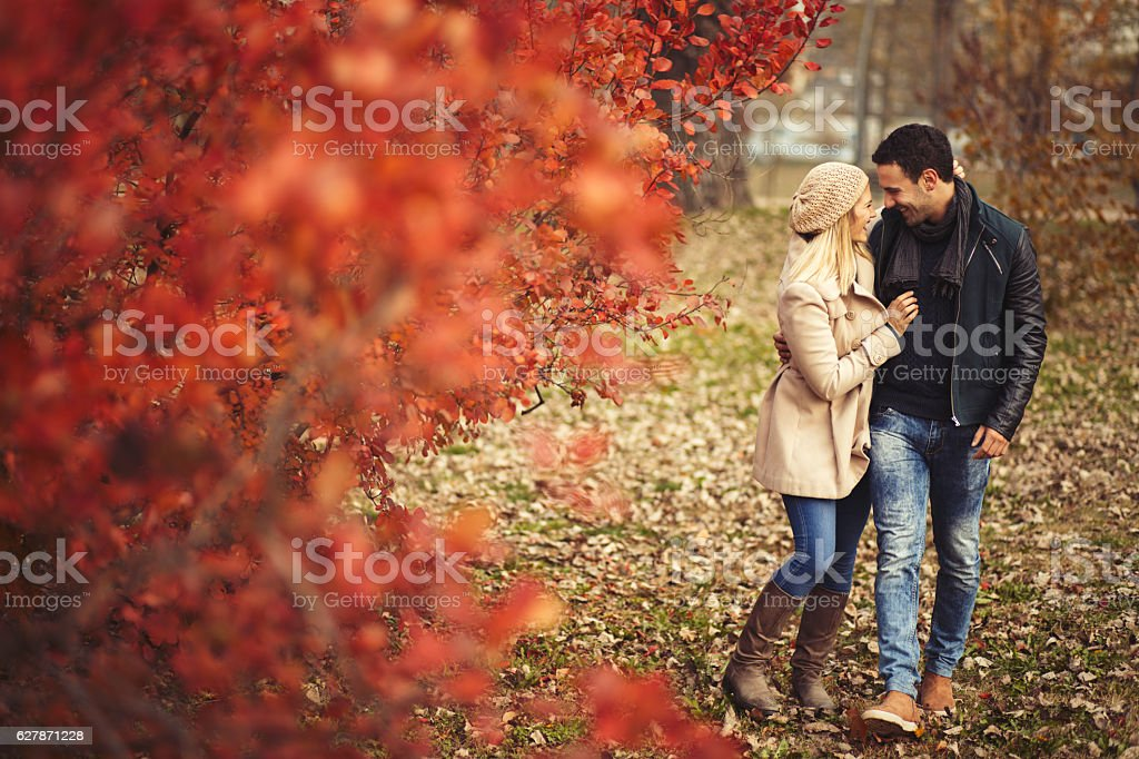 Young embraced couple taking a walk in autumn park. - foto de acervo