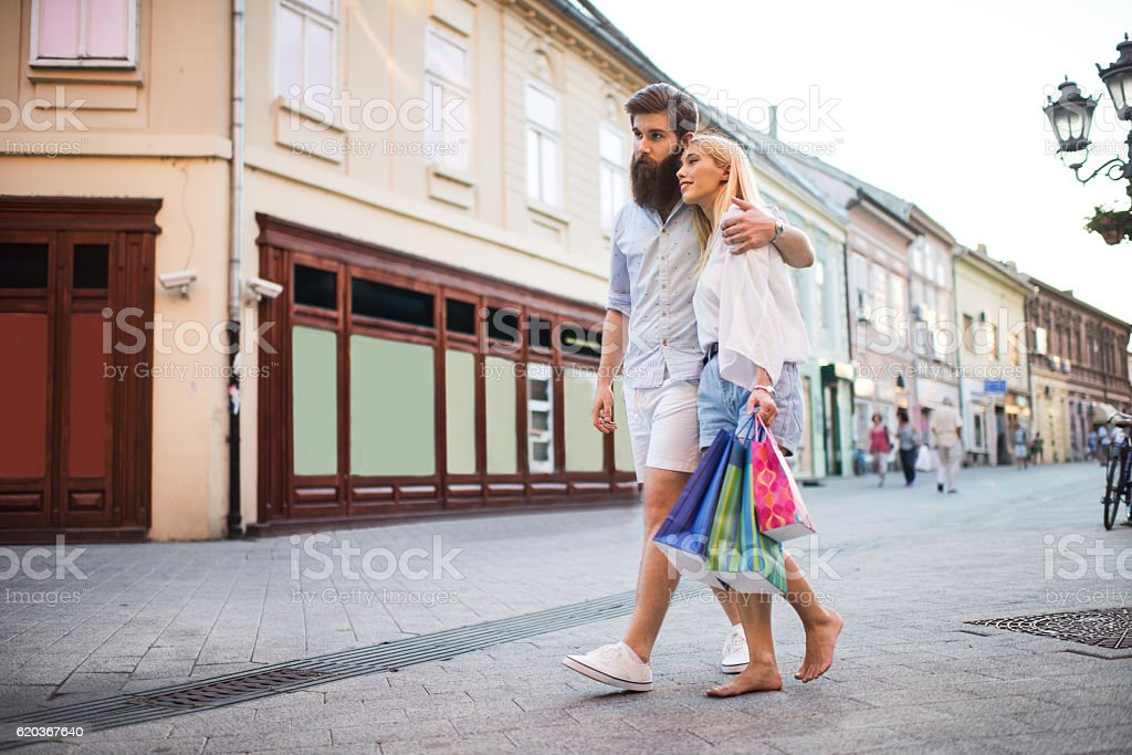 Young embraced couple taking a walk on the street. foto de stock royalty-free