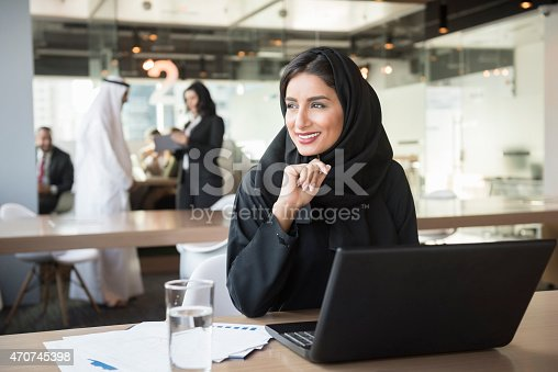 A photo of smiling Emirati businesswoman with laptop. Middle Eastern professional in traditional arab attire of abaya and hijab. She is sitting at conference table. Office worker is looking away while working in brightly lit office.Dubai, United Arab Emirates.
