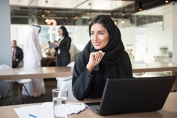 Young Emirati businesswoman looking away at conference table stock photo