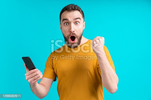 1032204252 istock photo Young emotional bearded man with smartphone in hand celebrating money win after betting at bookmaler's website using mobile application 1255032511