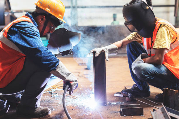 Young employee holding the metal steady as the senior welds it with another piece stock photo