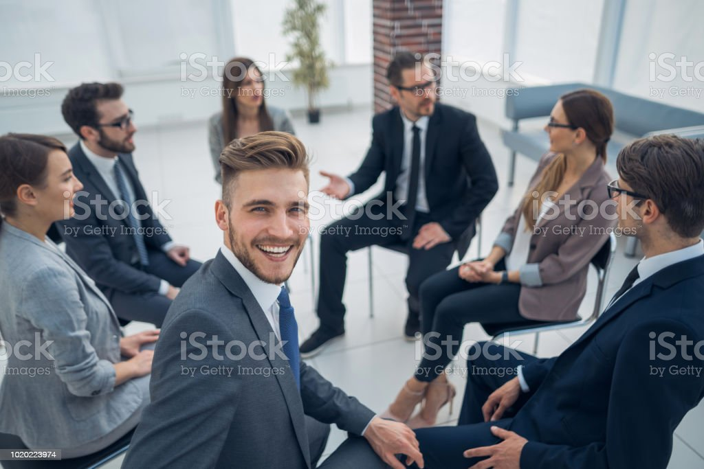 young employee sitting in a circle with business team stock photo
