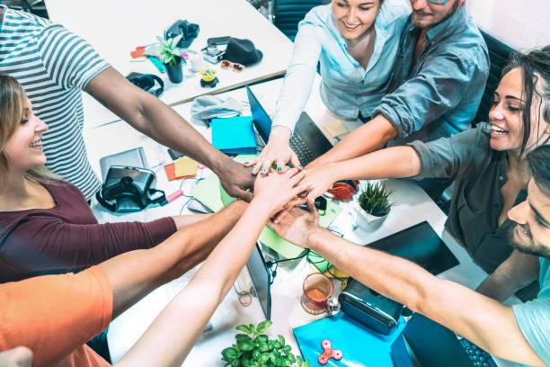 Young employee startup workers stacking hands at urban studio workspace on entrepreneurship brainstorming project - Business motivation concept with human resources on working time - Azure filter stock photo