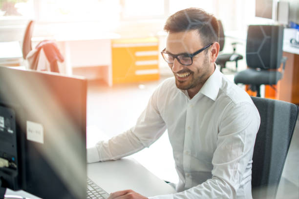Young employee with eyeglasses using computer at office stock photo