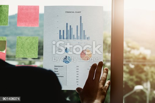 istock Young employees are analyzing the company's expenses using bar graph paper and posting at work his. 901406074