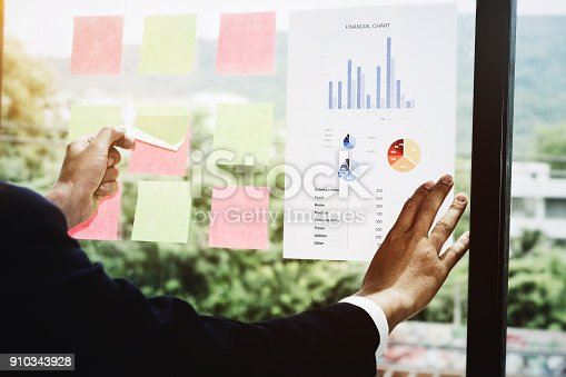 istock Young employees are analyzing the company's expenses using bar graph paper and posting at work his. 910343928