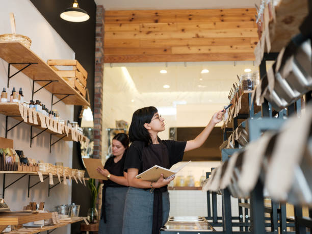 Young employees doing inventory with notebooks in store stock photo