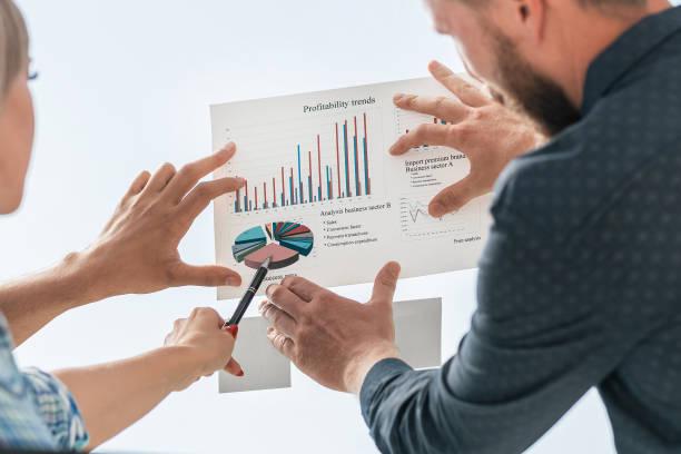 junge Mitarbeiter, die auf das Finanzdiagramm zeigen – Foto