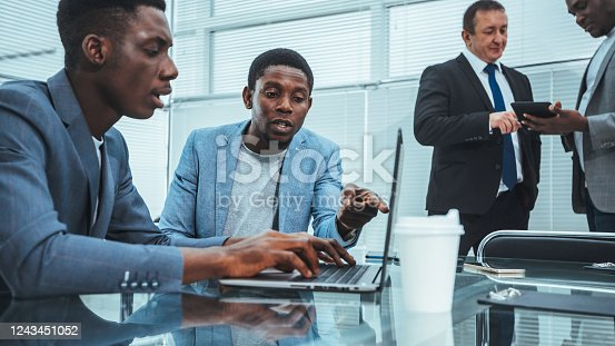 1124783373 istock photo young employees using a laptop in the office 1243451052