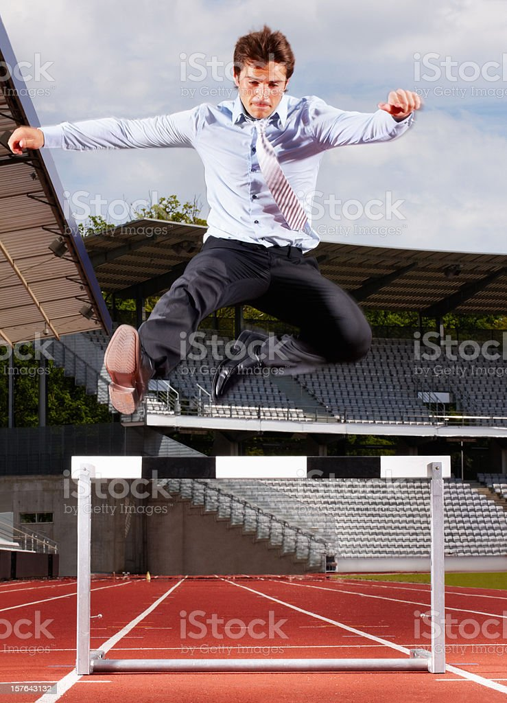 Young energetic businessman jumping over the hurdle royalty-free stock photo