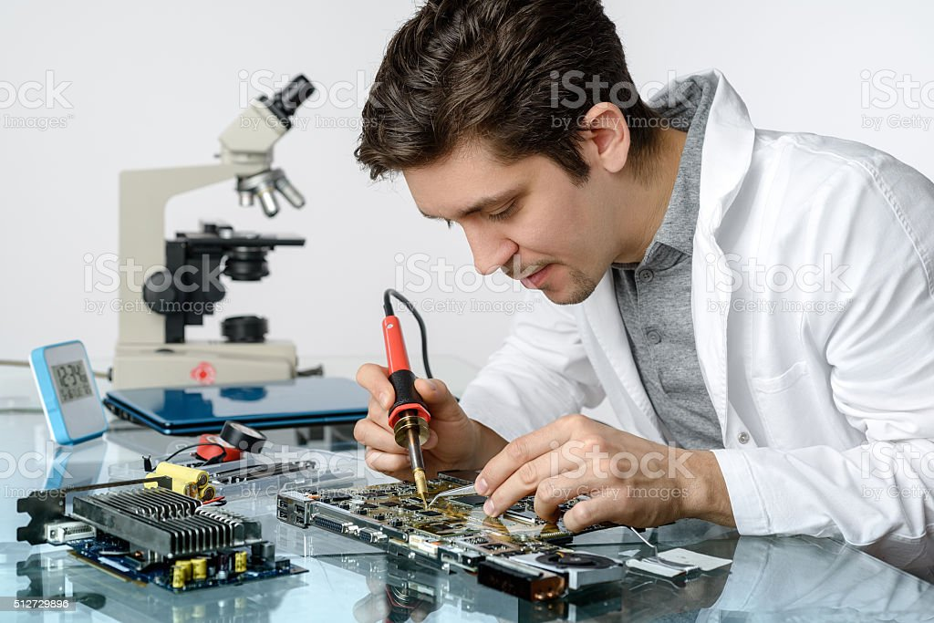 Young energetic male tech fixes electronic device stock photo