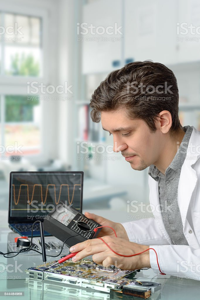 Young energetic male tech fixes motherboard stock photo