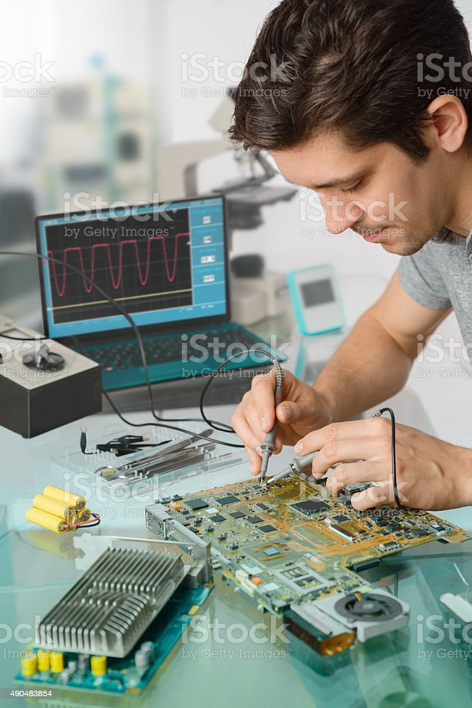 Young energetic male tech or engineer repairs electronic equipme stock photo