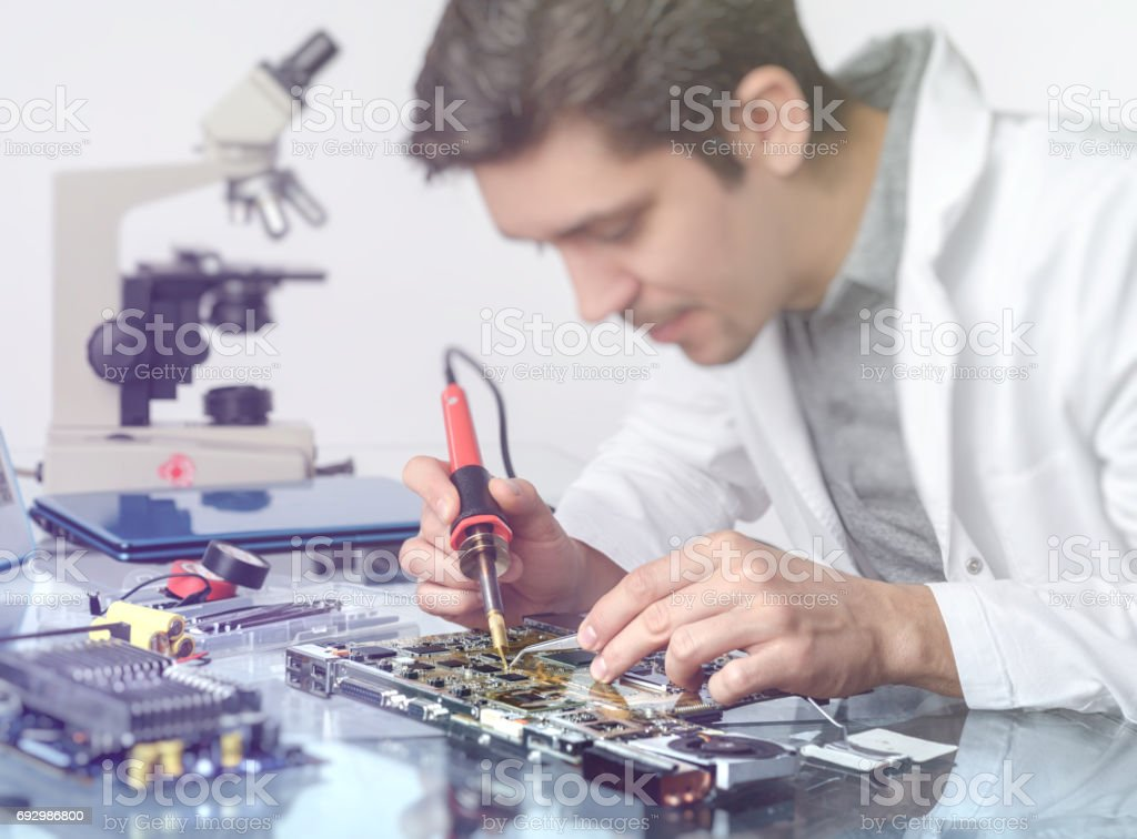 Young energetic male tech or engineer repairs electronic equipment stock photo