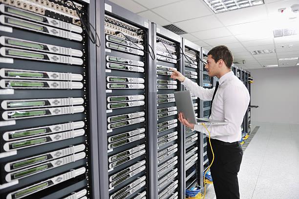young engeneer in datacenter server room stock photo
