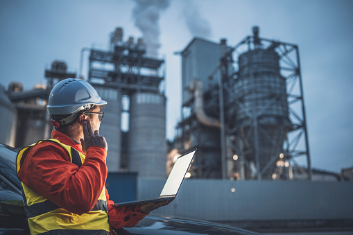 A side view of an young engineer wearing a helmet and using a laptop and hands free device to discuss a prolem with collegues during his night shirt in the oil rafinery. Engineering concept.