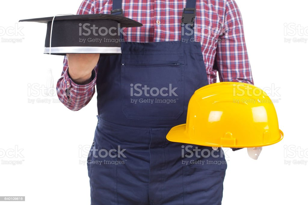 Young engineer holding his helmet and graduation hat stock photo