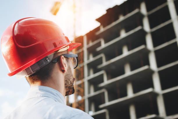 Junger Ingenieur in rot Helm prüft Bau des Gebäudes. Bärtige Geschäftsmann auf Hintergrund der Wolkenkratzer im Bau. Porträt von Bauingenieur am Bau Website Hintergrund – Foto