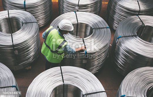 Overview of young quality inspector man checking production line and testing quality of steel pipe coils at warehouse section in cable factory. XXXL