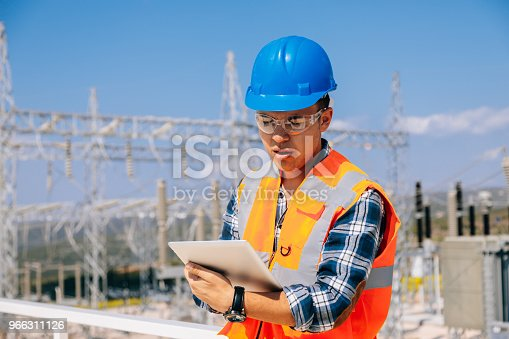 Portrait of young caucasian technician engineer man wearing white worker headwear standing, working, checking farm field system and looking up verify at wind turbine while using digital tablet pc computer for renewable energy plan by wind turbine power generation station in rural landscape. xxxl size