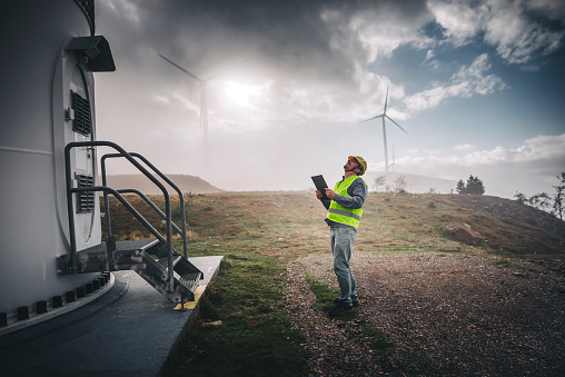 Portrait of young caucasian technician engineer man wearing yellow worker headwear standing, working, checking wind farm field system and looking up verify at wind turbine while using a radio station energy plan by wind turbine power generation station