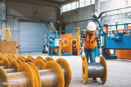 Skilled young heavy industry engineering worker man loading and working with punching bobbin metal reel cable drum reel wire spools with safety workwear and moving a massive metal construction object in warehouse of factory. XXXL size