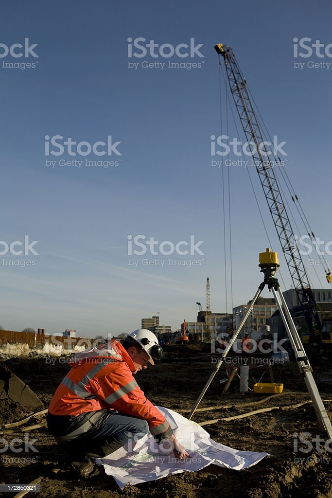 Young engineer on construction site controlling the foundation royalty-free stock photo