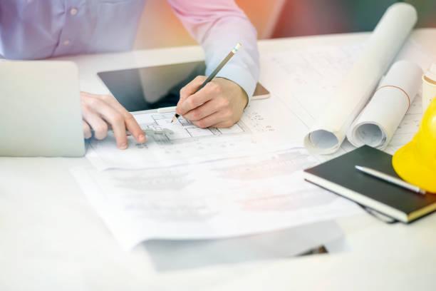 Joven ingeniero o arquitecto, trabajando con Blueprint y Laptop en su oficina. - foto de stock
